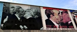 """Эта карикатура базируется на очень популярной в новой демократической Германии документальной фотографии, гда Брежнев и Хоннекер обмениваются страстным поцелуем. Подпись говорит: """"Господи, помоги мне выжить среди этой смертной любви""""."""